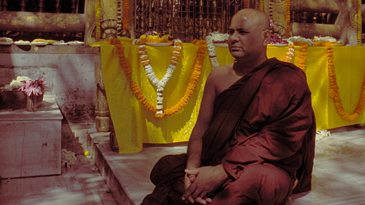 Monk in red robe, sitting cross-legged in front of saffron-draped altar with offerings.