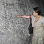 "Woman points to inscription on rock. If you can read Brahmi, you will know she is pointing at the word ""dharma"" or ""virtue/ethic/moral""."