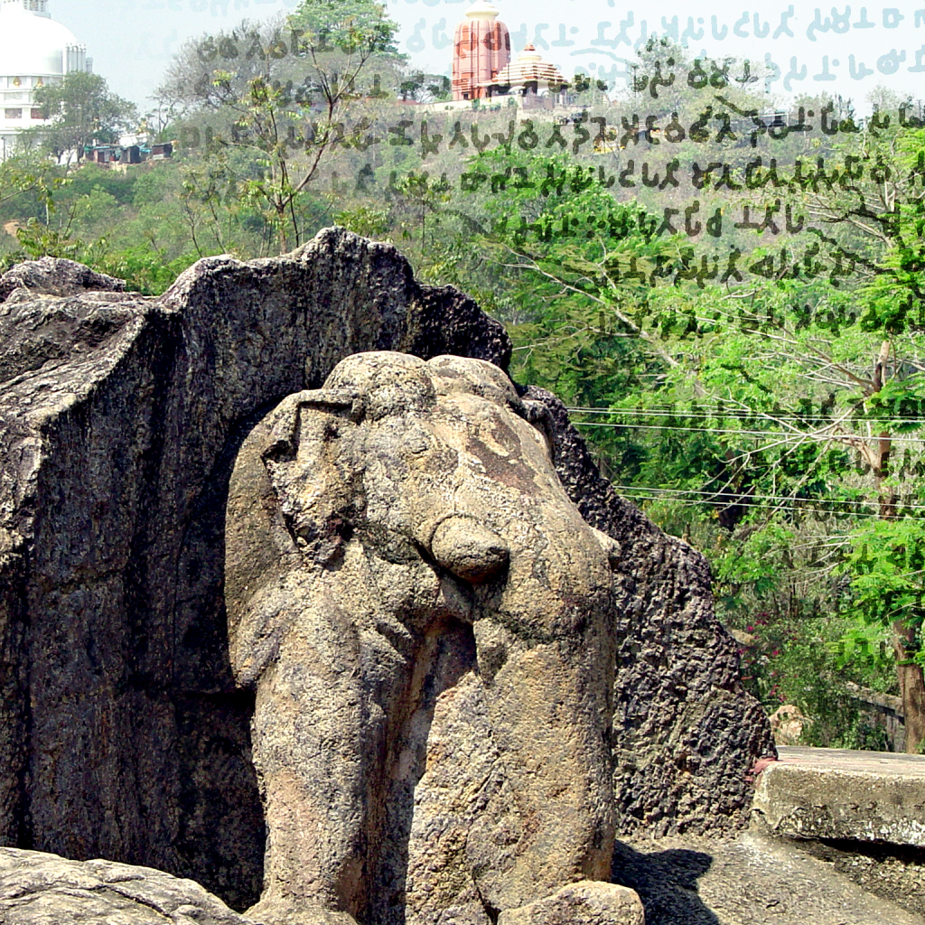 "A sculptured elephant walks out of the stone. Brahmi ""pinman"" script is superposed on the background. There is a Buddhist pagoda in the background."
