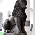 Dark sandstone lion statue, sitting up.