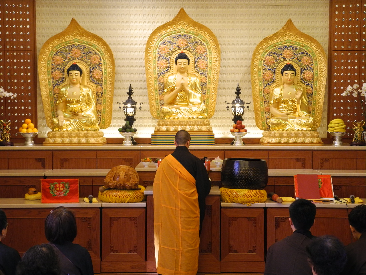 Woman in saffron robe stands before three Buddhas