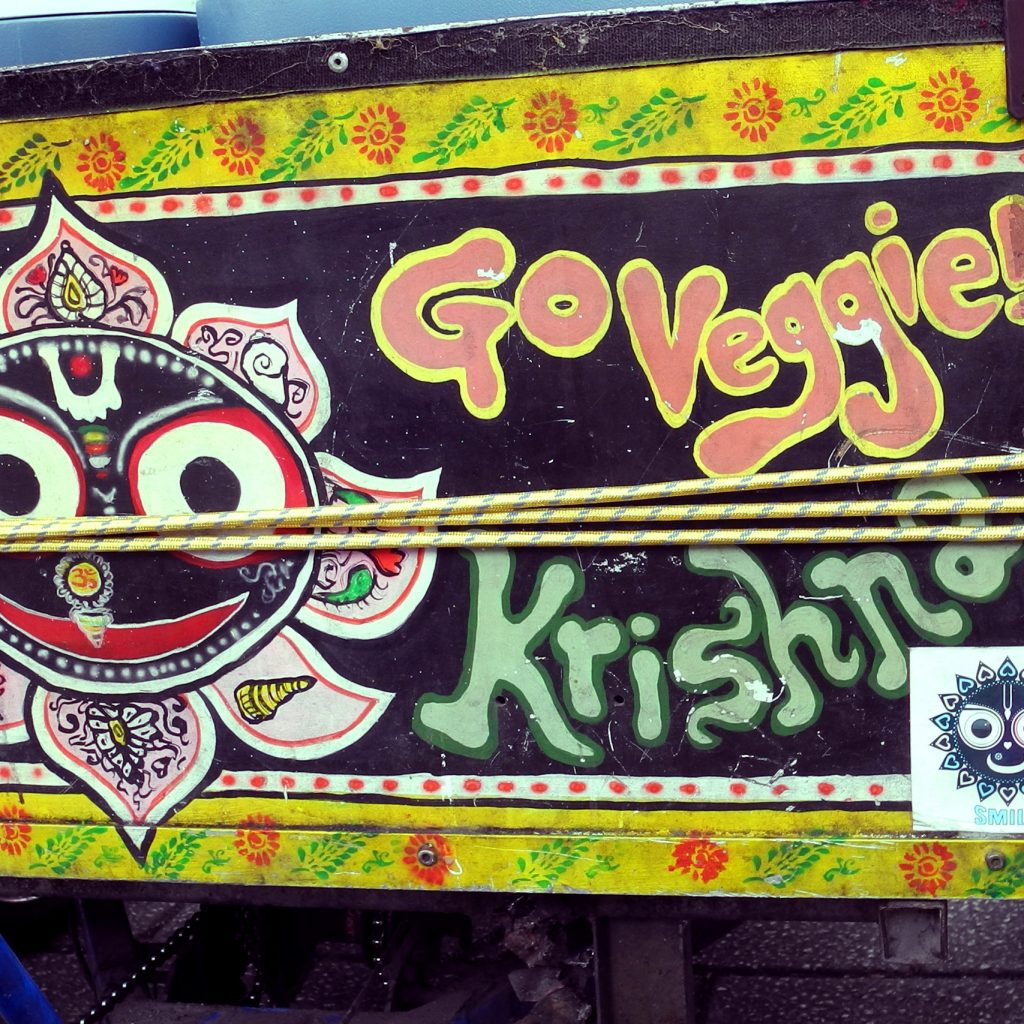 "An east Indian Jagannath image of Krishna and the words ""Go veggie!"" and ""Krishna"" are painted on the side of a cart."
