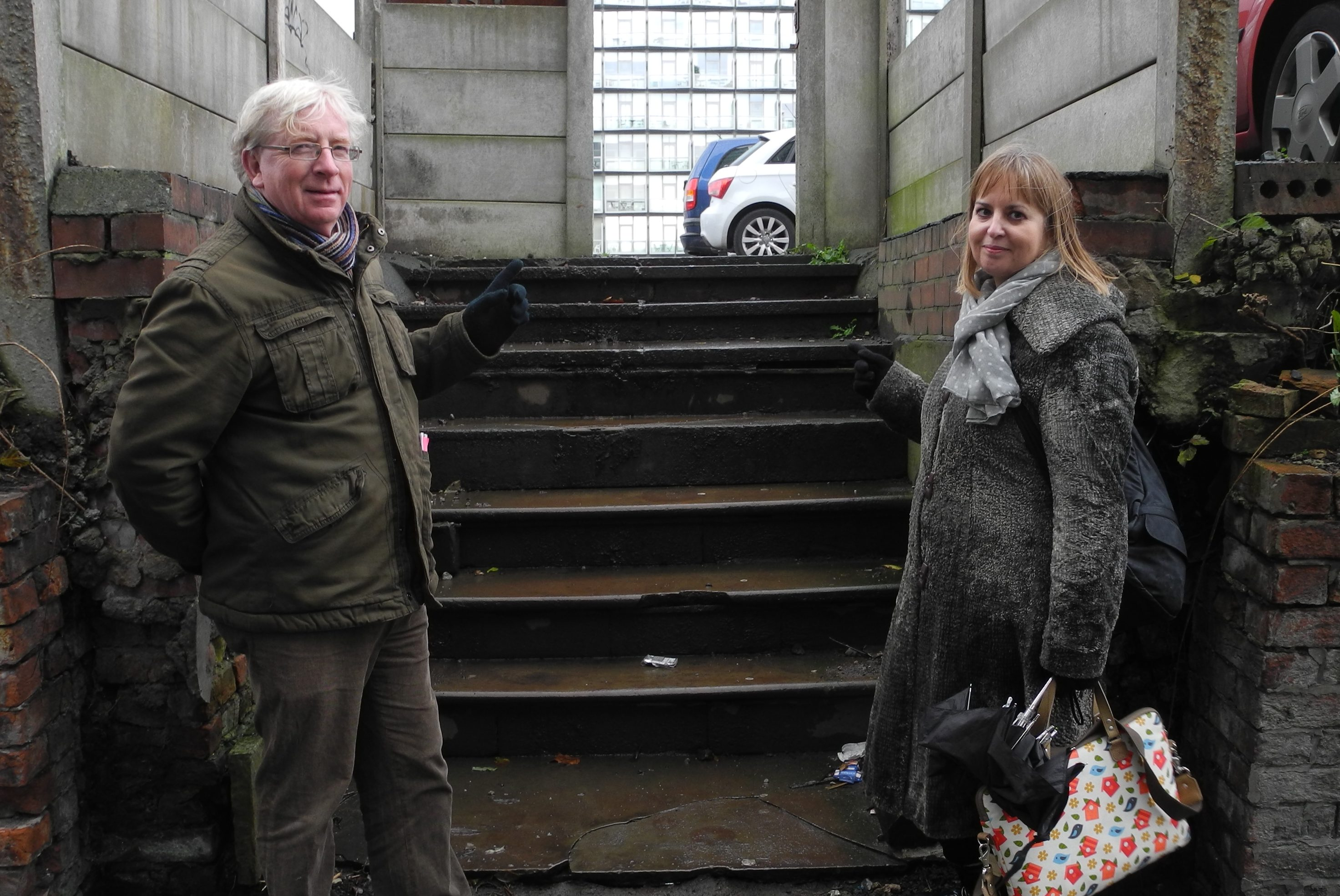 A man and a woman point to some stone steps up to a car park