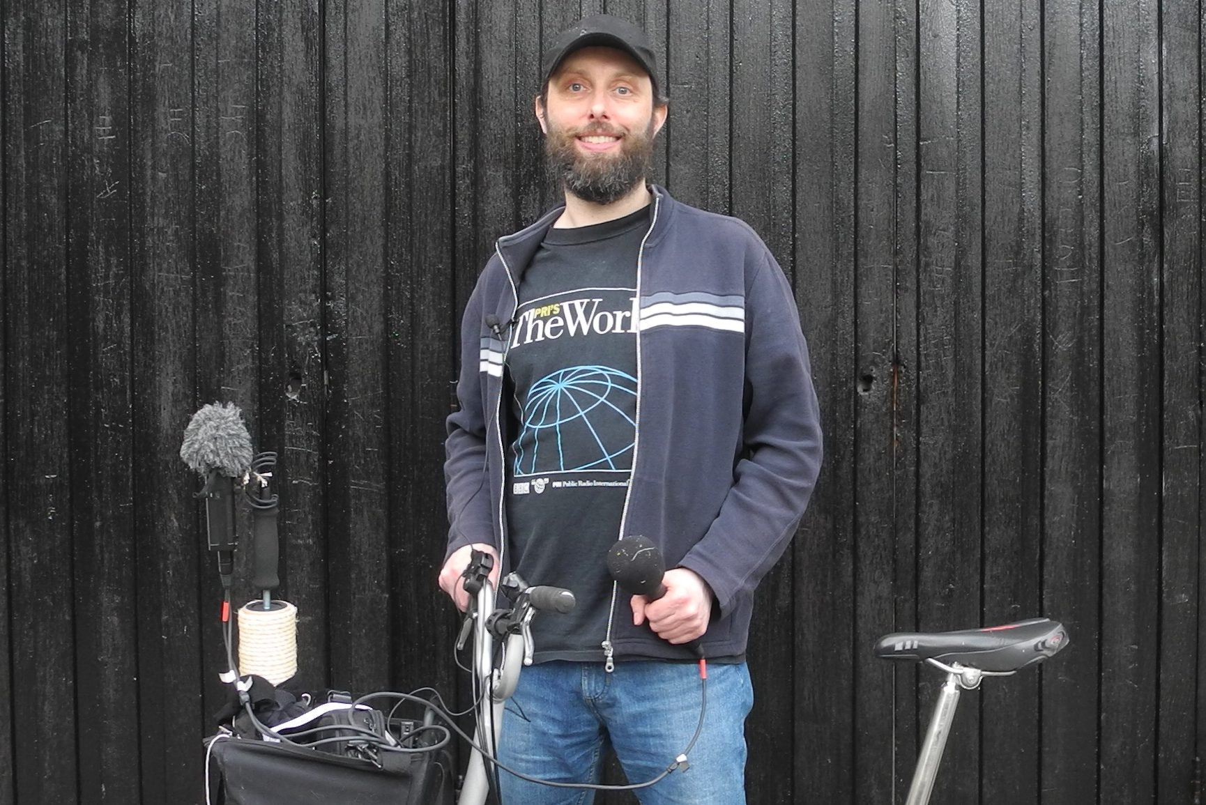 Man with cap, bike, and microphones