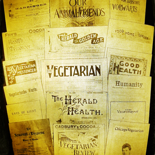 An old photograph of over a dozen vegetarian magazines