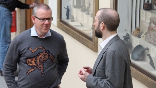 Man in jumper with Greek mosaic design talks to Ian by cases of ancient Greek artefacts.