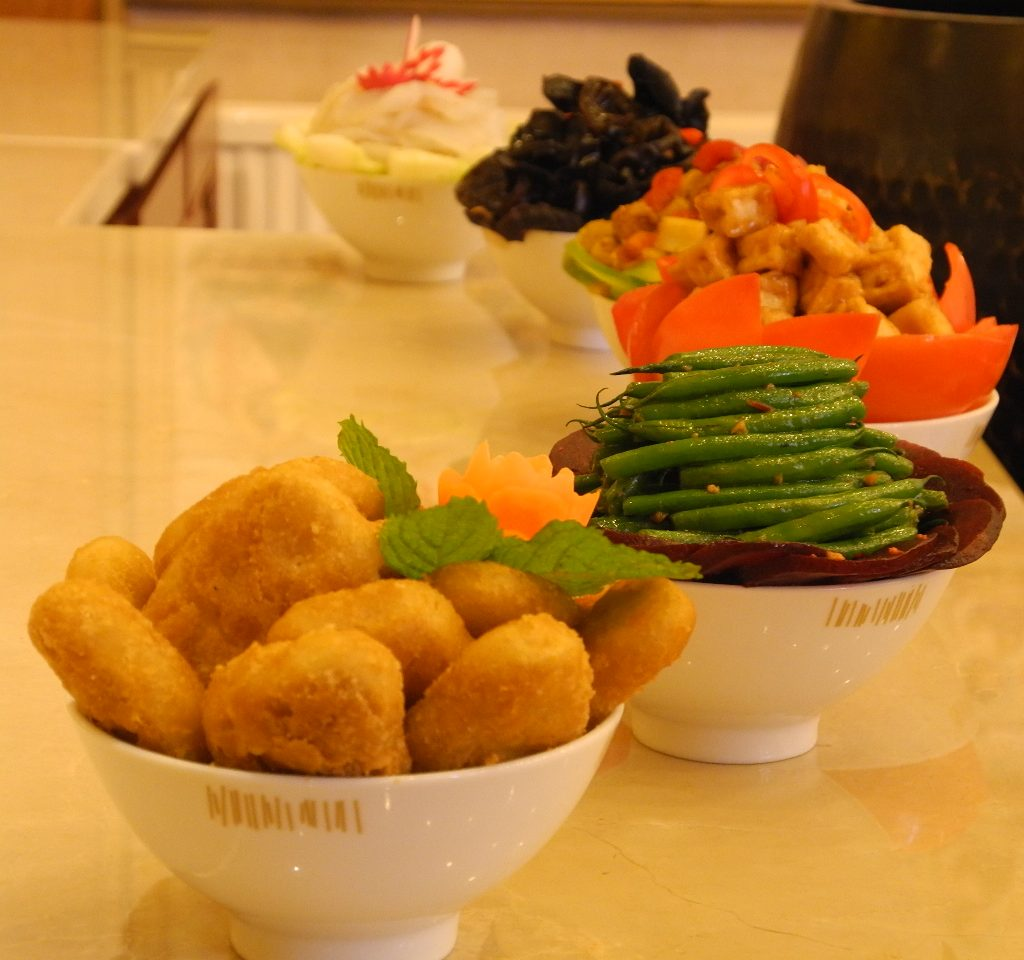 Various vegan foods, such as green beans and tofu, in bowls in a row