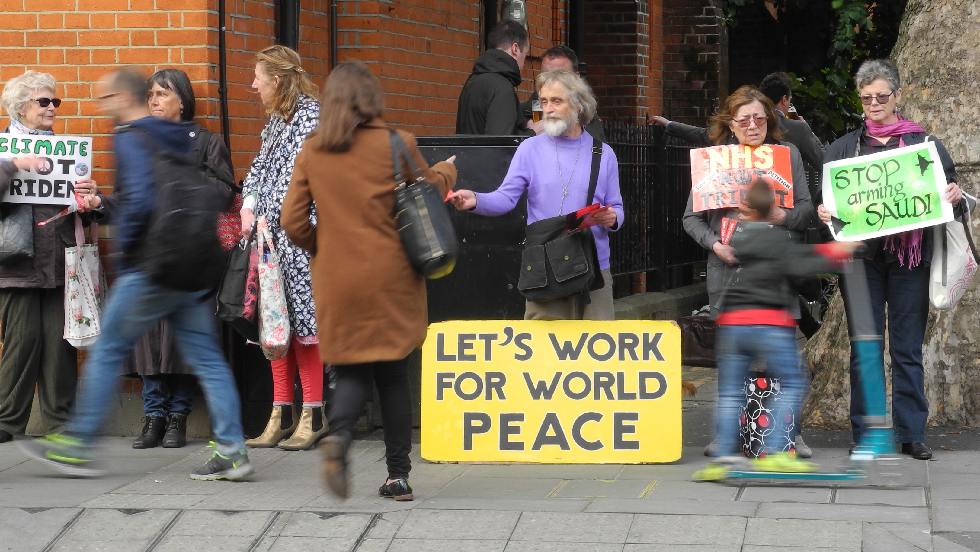 "6 people on pavement holding signs and leaflets. Big sign: ""Let's work for world peace"""